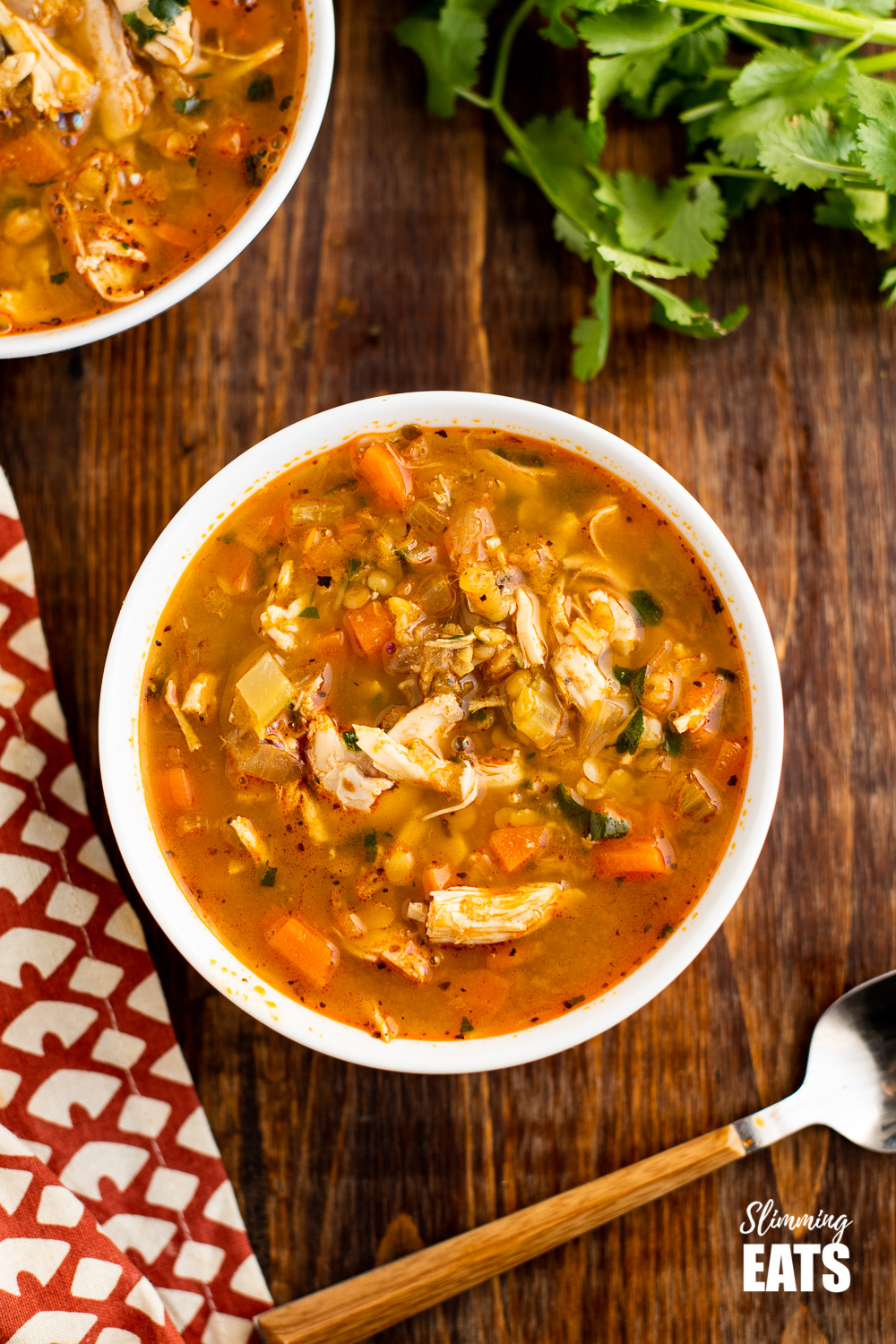 over the top view of chicken and lentil soup in white bowl on wooden board