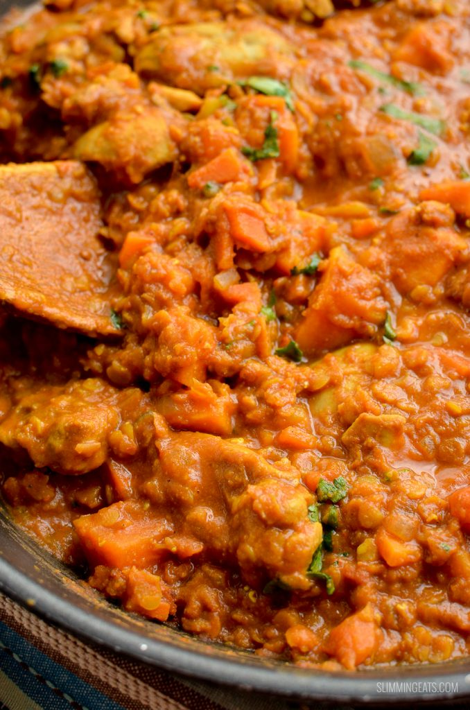 close up of chicken, sweet potato and lentil curry in skillet with wooden spoon