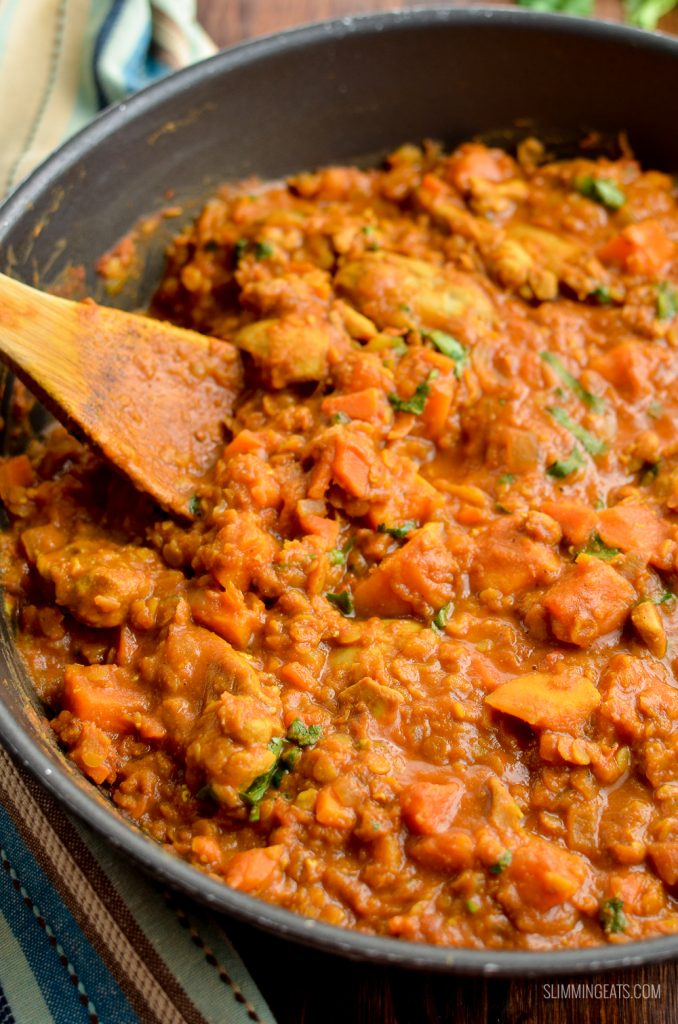 chicken, sweet potato and lentil curry in skillet with wooden spoon