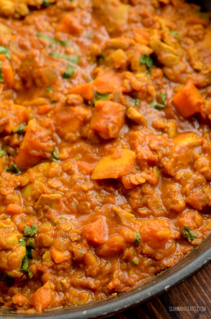 close up of chicken, sweet potato and lentil curry in skillet