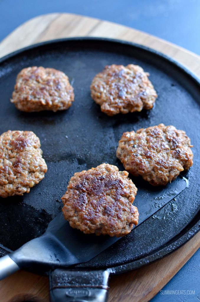 pork sausage breakfast patties on black skillet with spatula