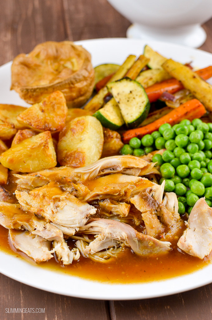 plated up slow cooked chicken with gravy and roast potatoes, Yorkshire pudding and vegetables