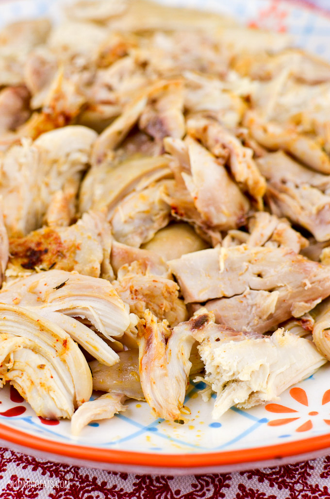 close up of shredded whole slow cooker cooked shredded chicken on a oval plate