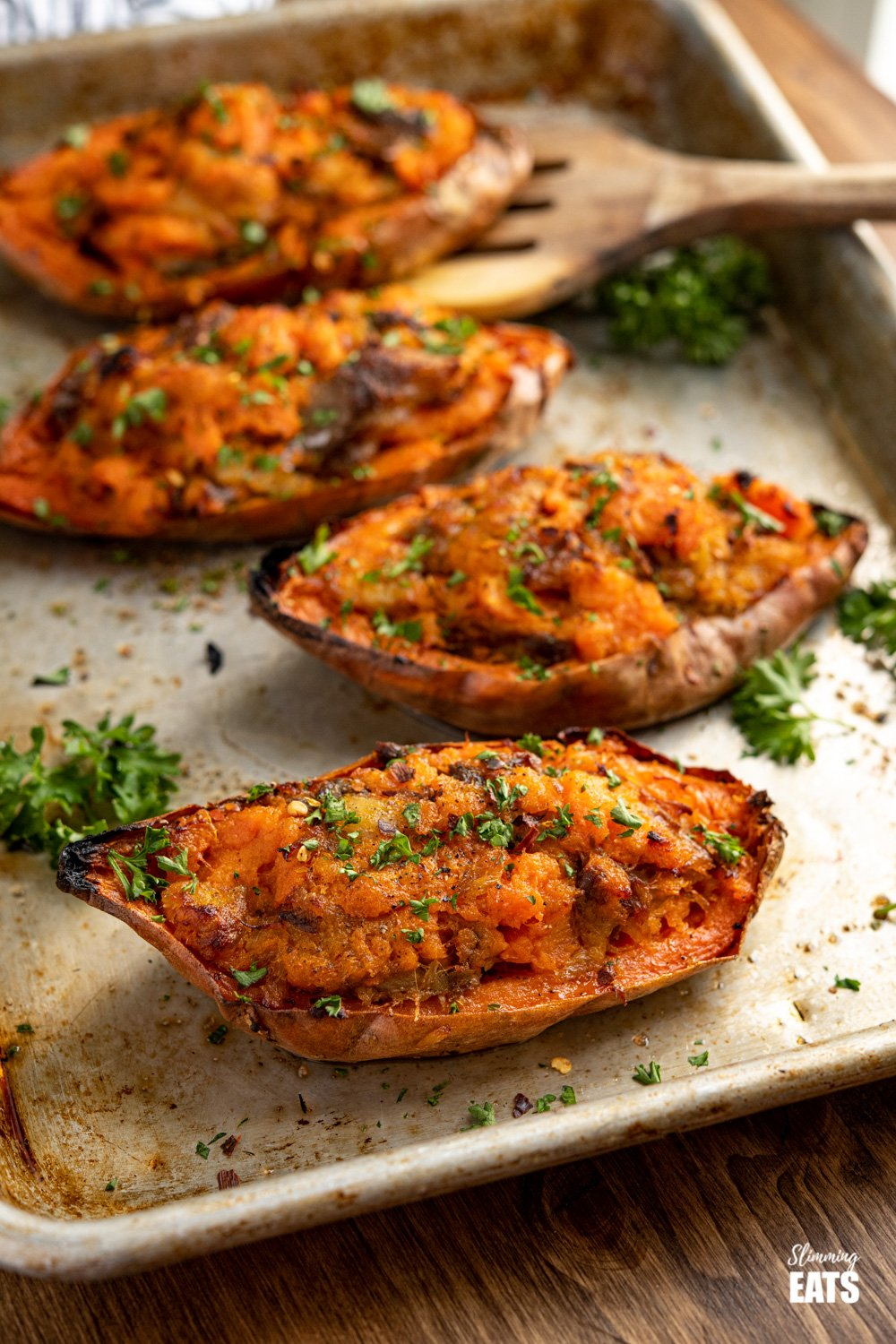 double baked smoked mackerel stuffed sweet potatos on a baking tray with wooden spatula