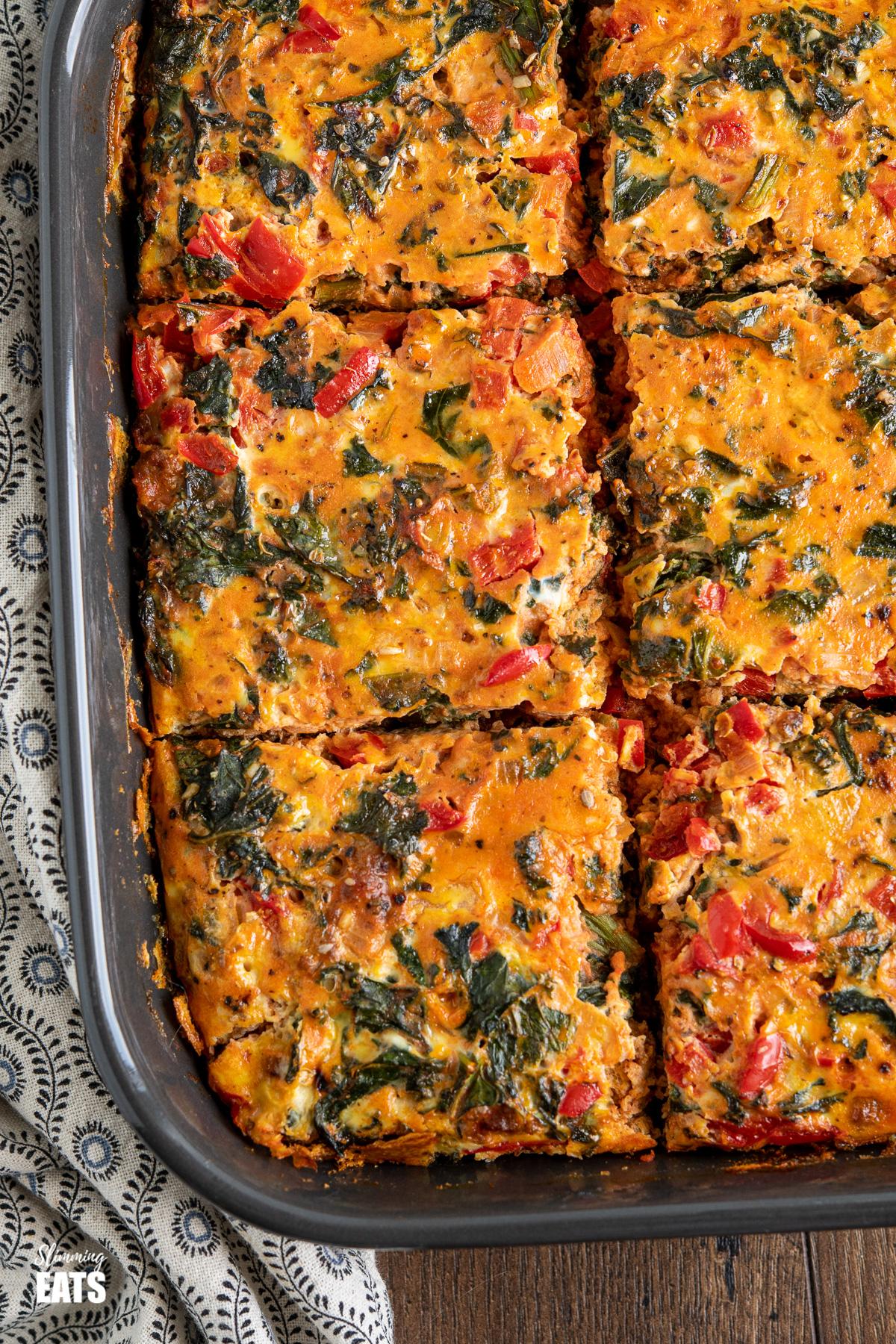 sliced Breakfast Layered Crustless Quiche in dark grey baking dish