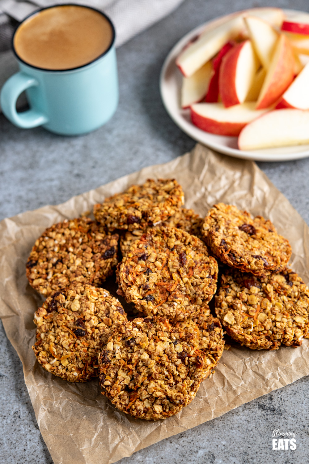 carrot cake flapjack cookies on parchment paper with mug of espresso coffee and sliced apple on white plate.