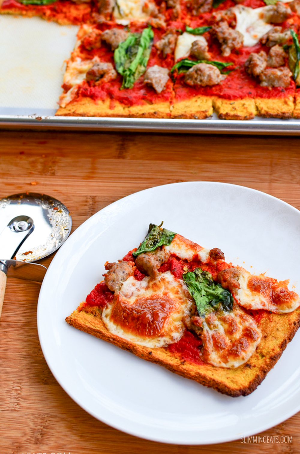 slice of cauliflower pizza on white plate with pizza on tray and pizza cutter