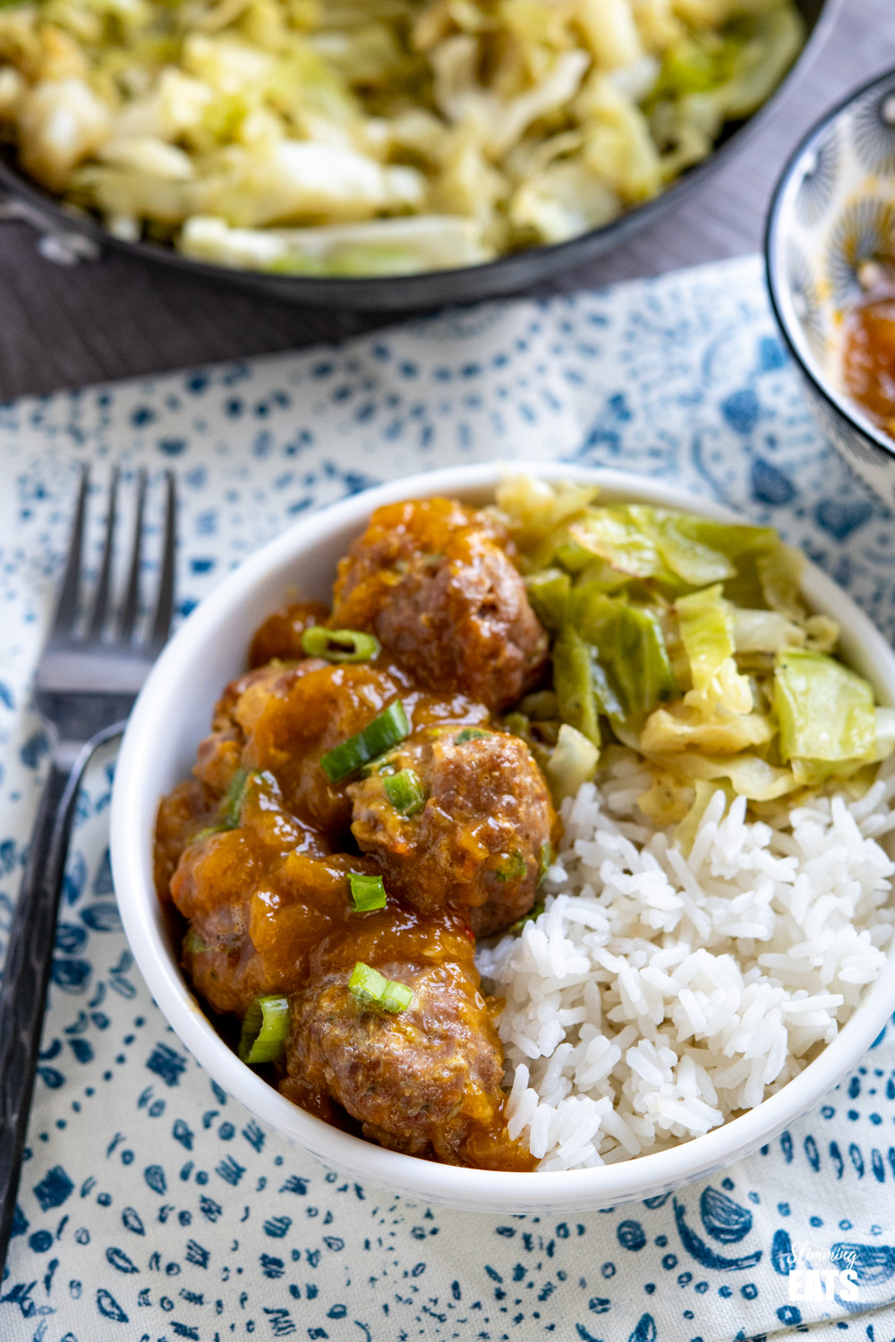 chicken mango meatballs and with spicy mango sauce, rice and cabbage in white bowl