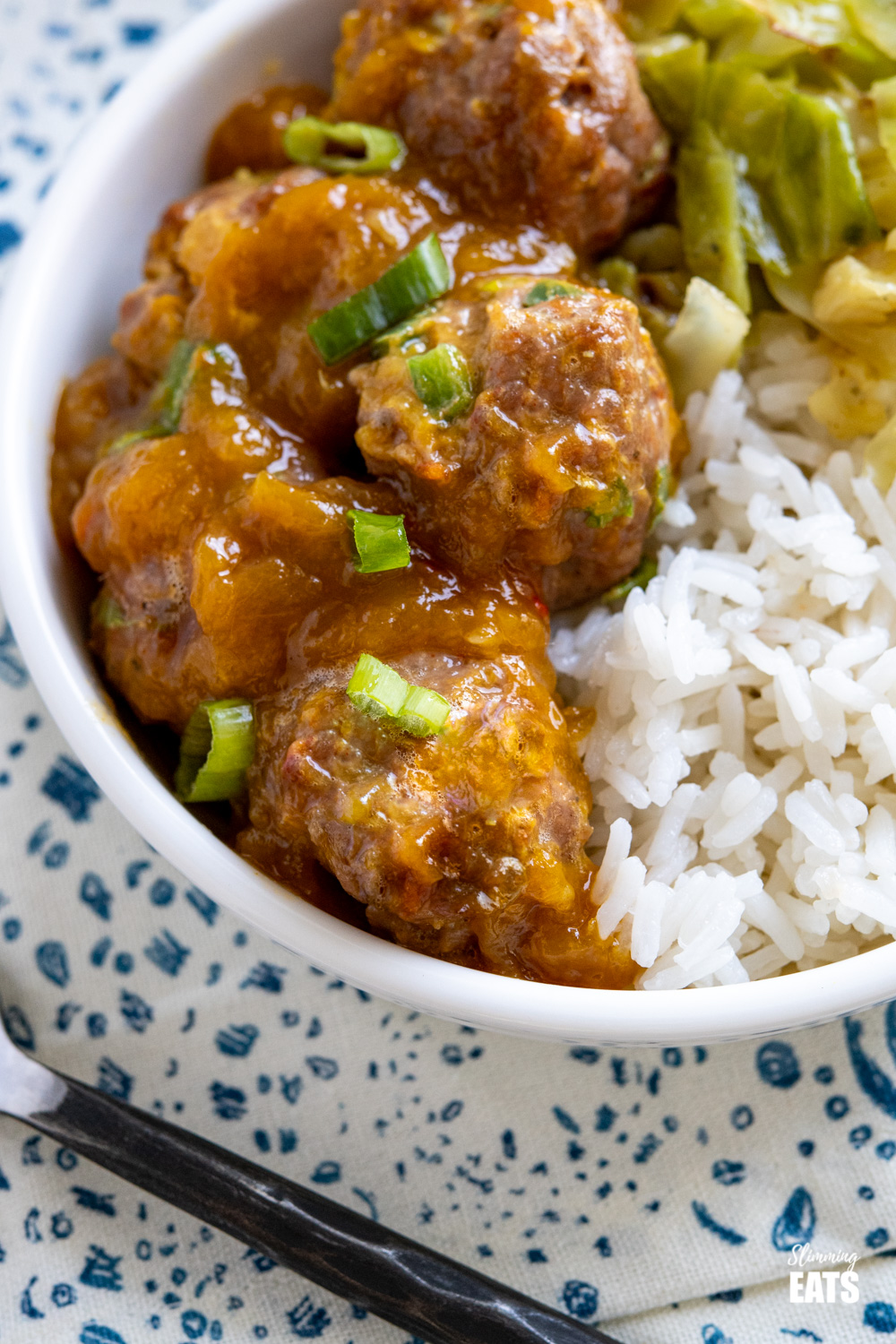 close up of chicken mango meatballs and with spicy mango sauce, rice and cabbage in white bowl