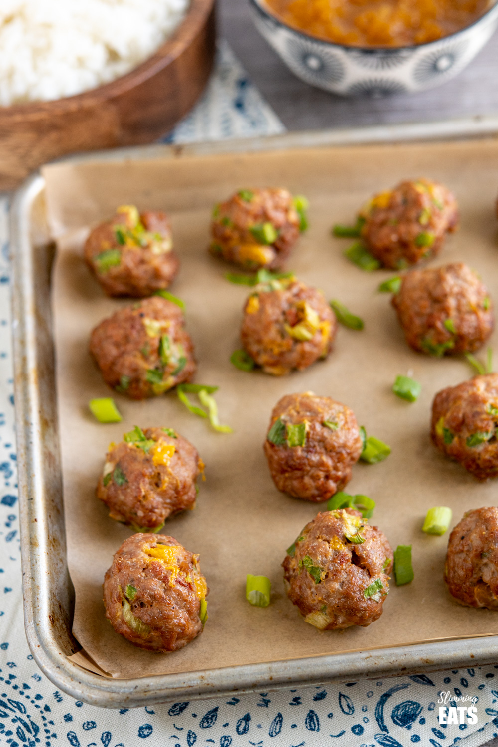 chicken and mango meatballs on a parchment lined tray