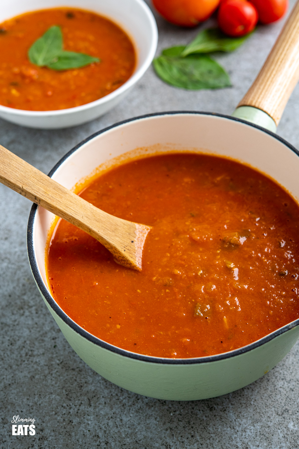 Fresh Tomato and Basil Soup in wooden handled cast iron saucepan with bowl of soup and fresh tomatoes in background