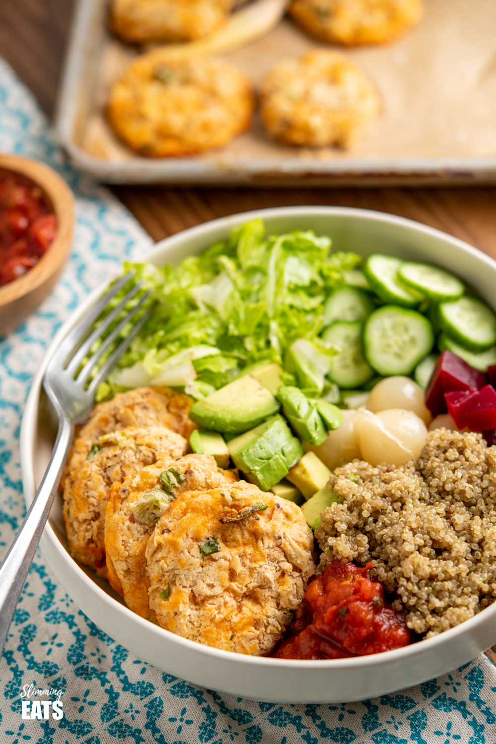 Cheddar Butter Bean Bites in cream bowl with quinoa, cucumber, lettuce, salsa, avocado, beets and picked onions