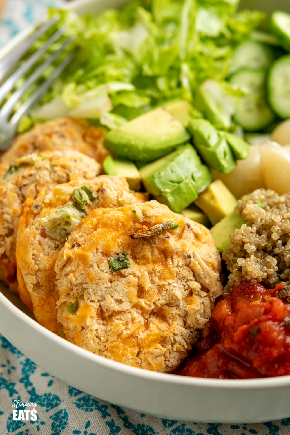 close up of Cheddar Butter Bean Bites in cream bowl with quinoa, cucumber, lettuce, salsa, avocado, beets and picked onions