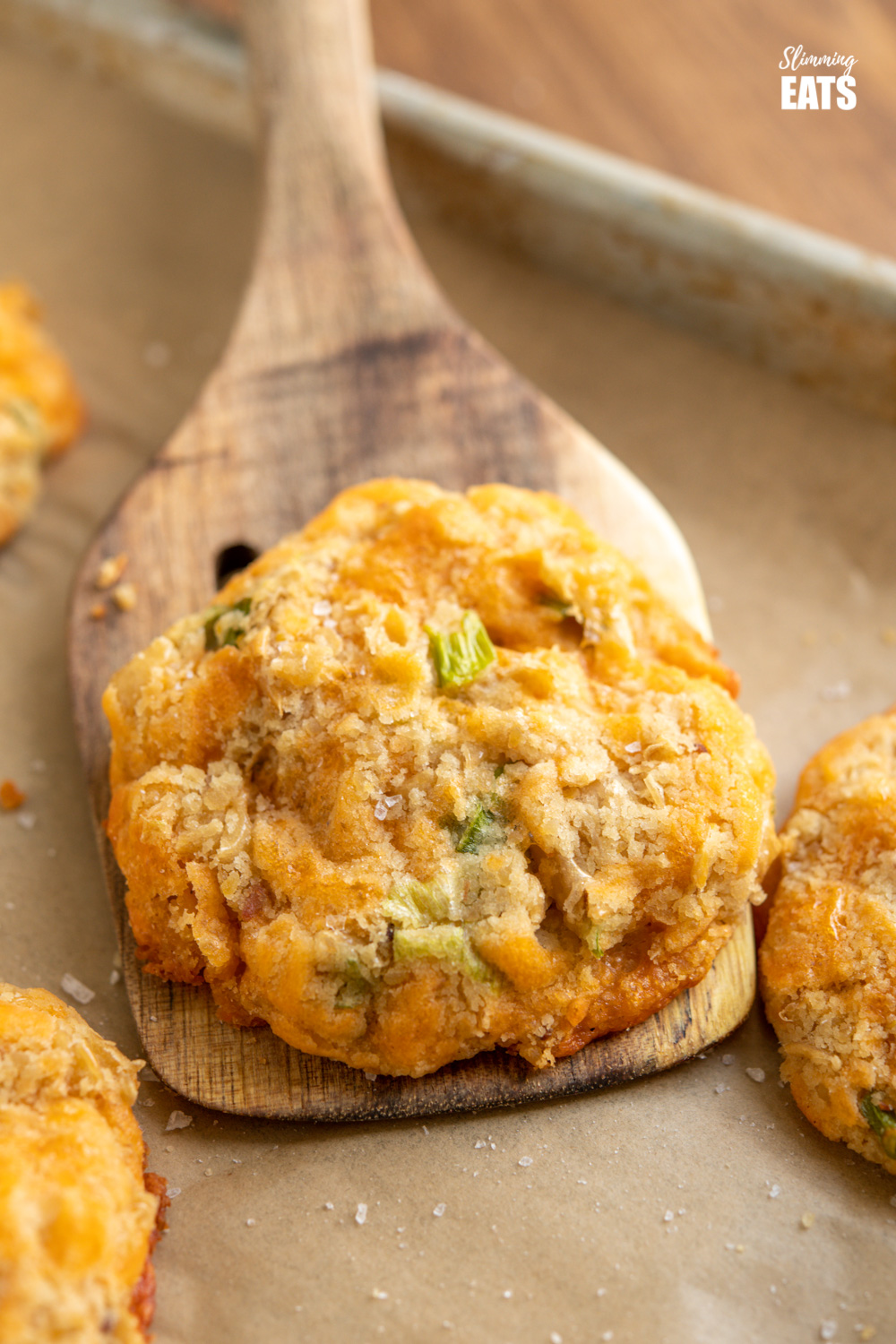 close up of cheddar butter bean bites on wooden spatula from parchment paper lined baking tray