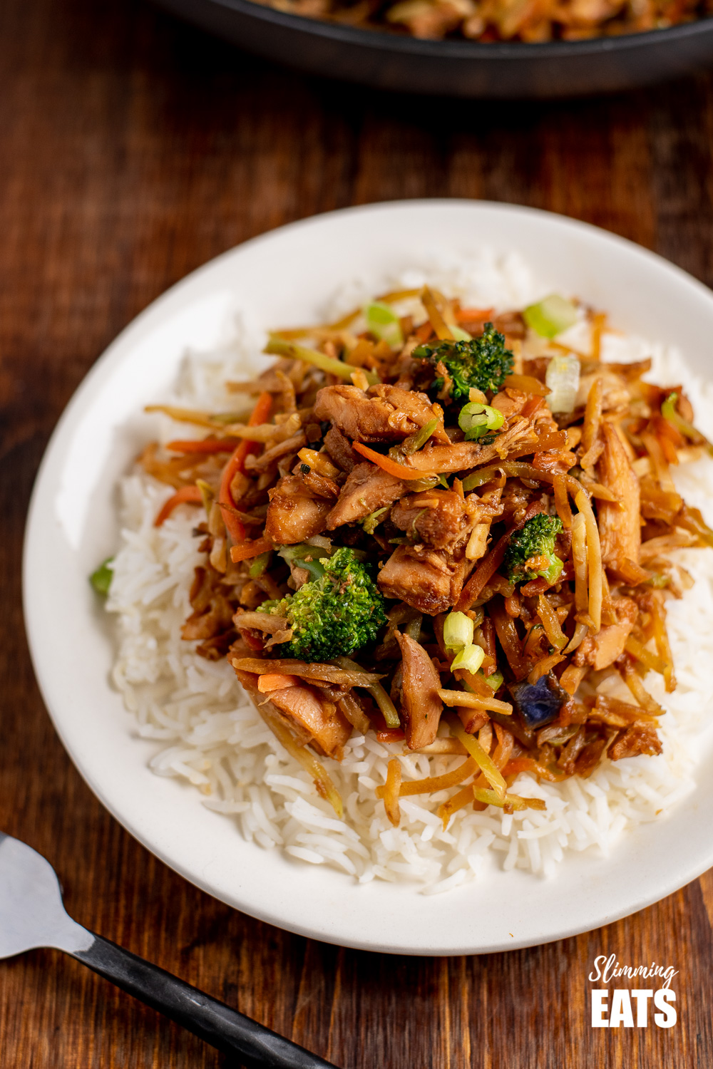 close up of orange and ginger turkey stir fry with rice on white plate