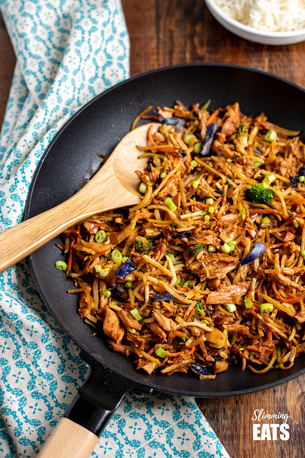 orange and ginger turkey stir fry in a black frying pan with wooden spoon