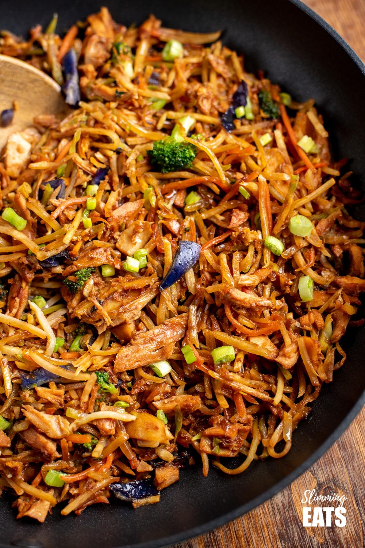 close up of orange and ginger turkey stir fry in black frying pan