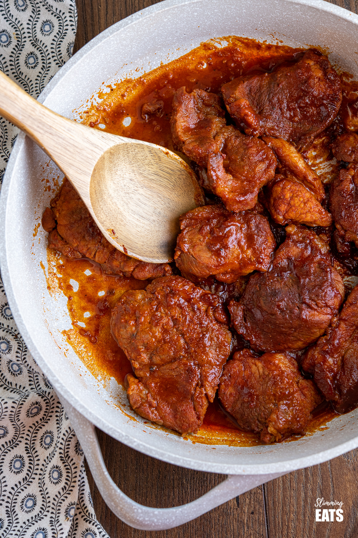 stove top bbq pork in pan with wooden spoon