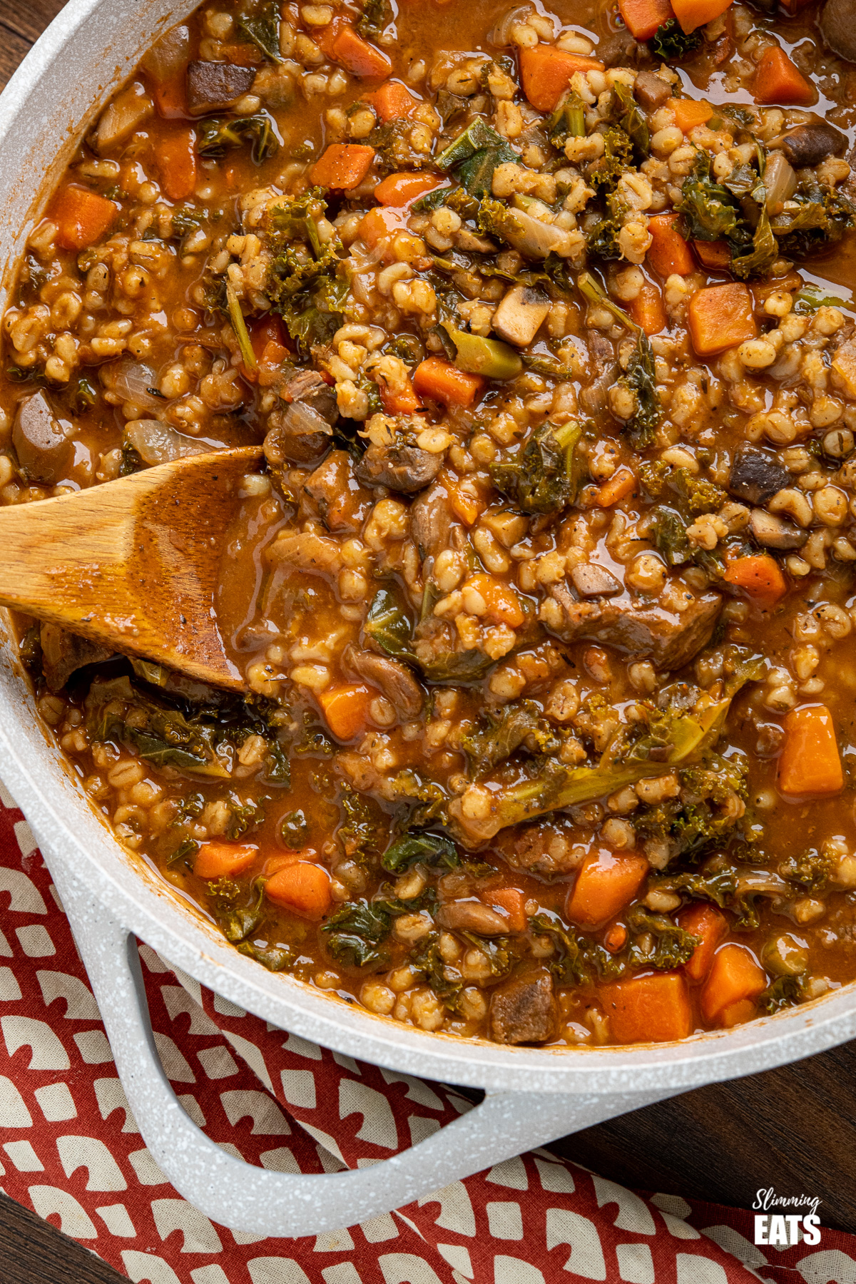 close up of Beef and barley stew in pot with wooden spoon