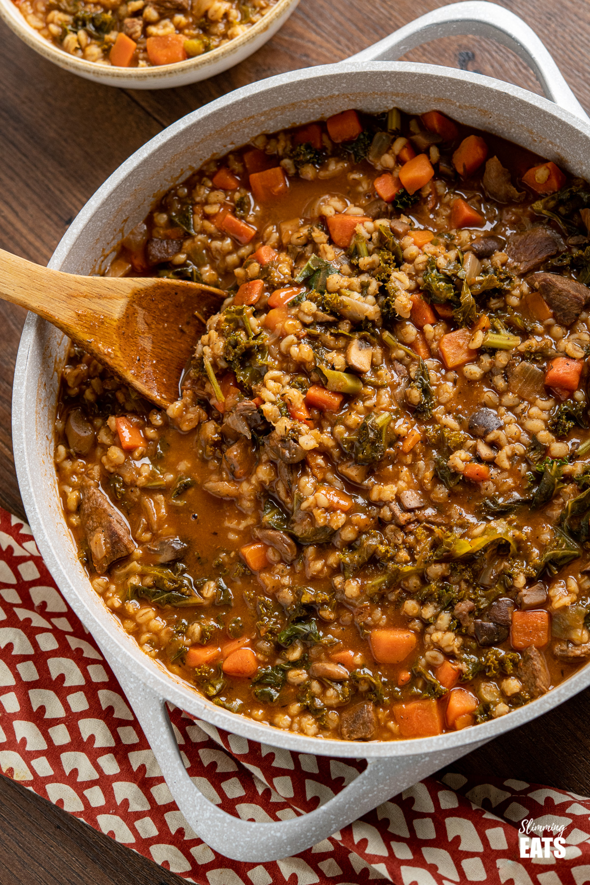 Beef and barley stew in pot with wooden spoon, bowl of stew in background