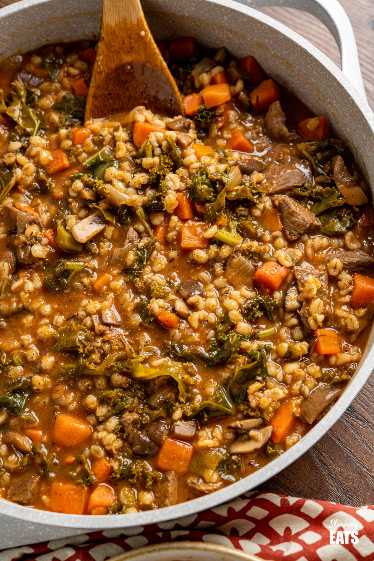 Beef and barley stew in casserole pot with wooden spoon