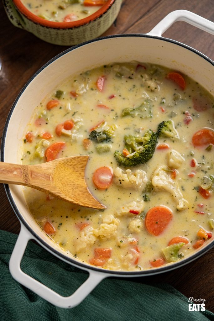 creamy vegetable soup in white cast iron pan with pale green ceramic bowl of soup in background