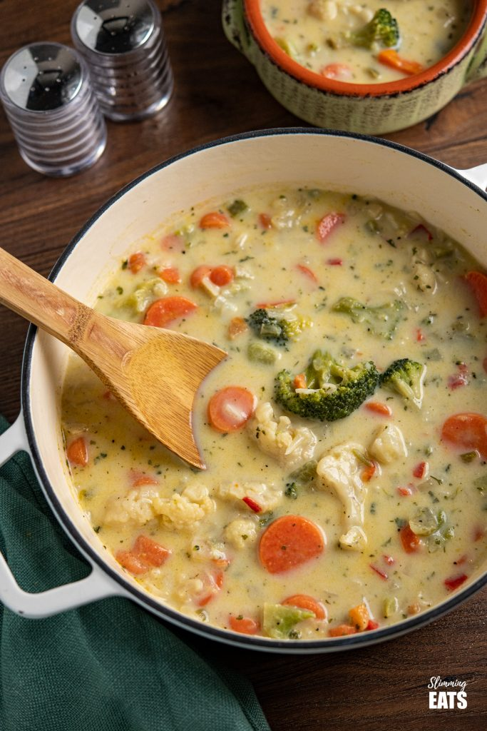 creamy vegetable soup in white cast iron pan with bowl of soup in background with salt and pepper shakers