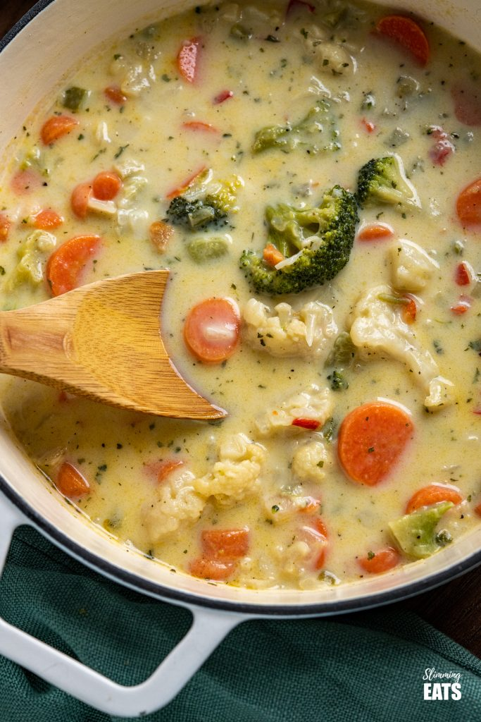 Close up of creamy vegetable soup in white cast iron pot