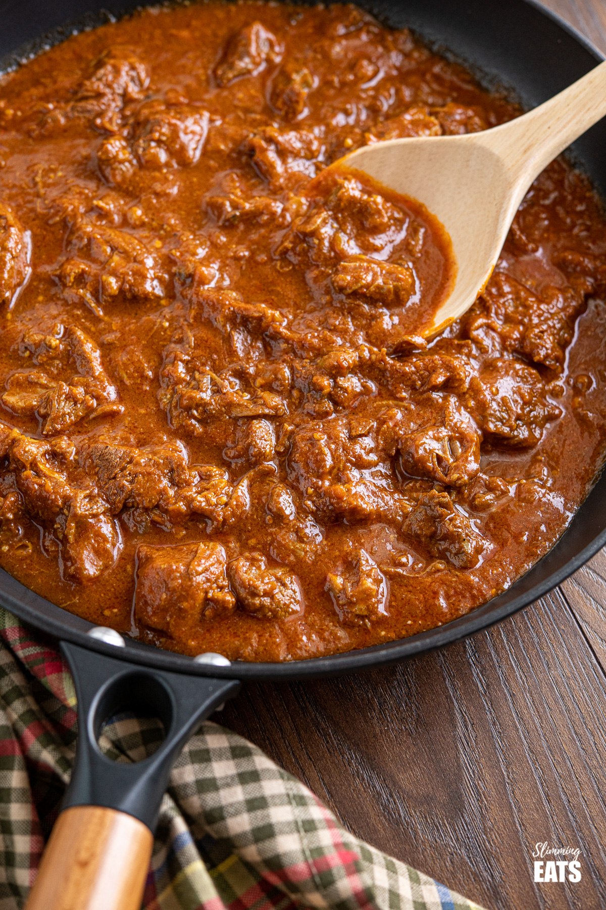 lamb rogan josh in black frying pan with wooden handle on wooden board, wooden spoon placed in pan
