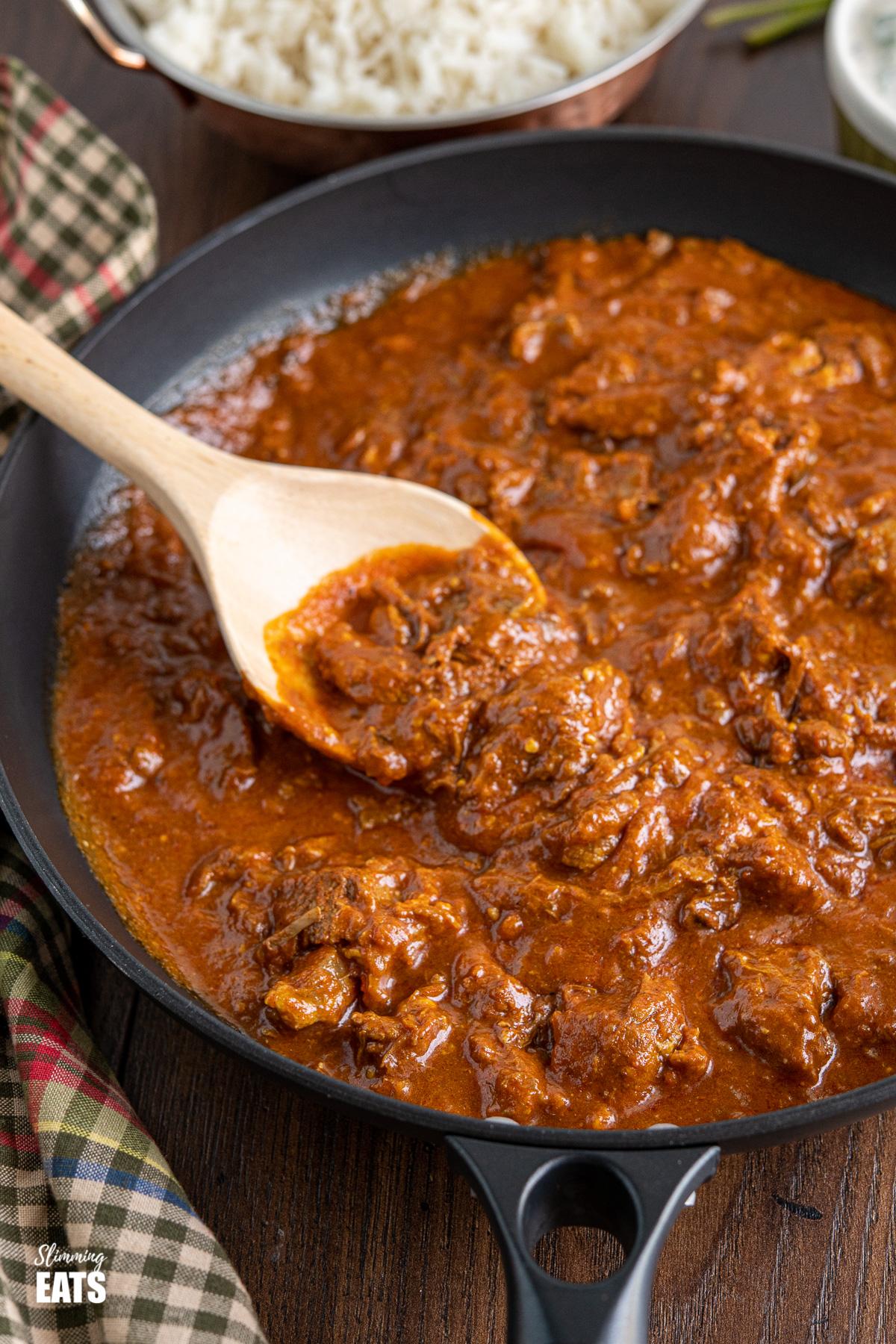 lamb rogan josh in black frying pan with wooden spoon, rice in background in metal dish
