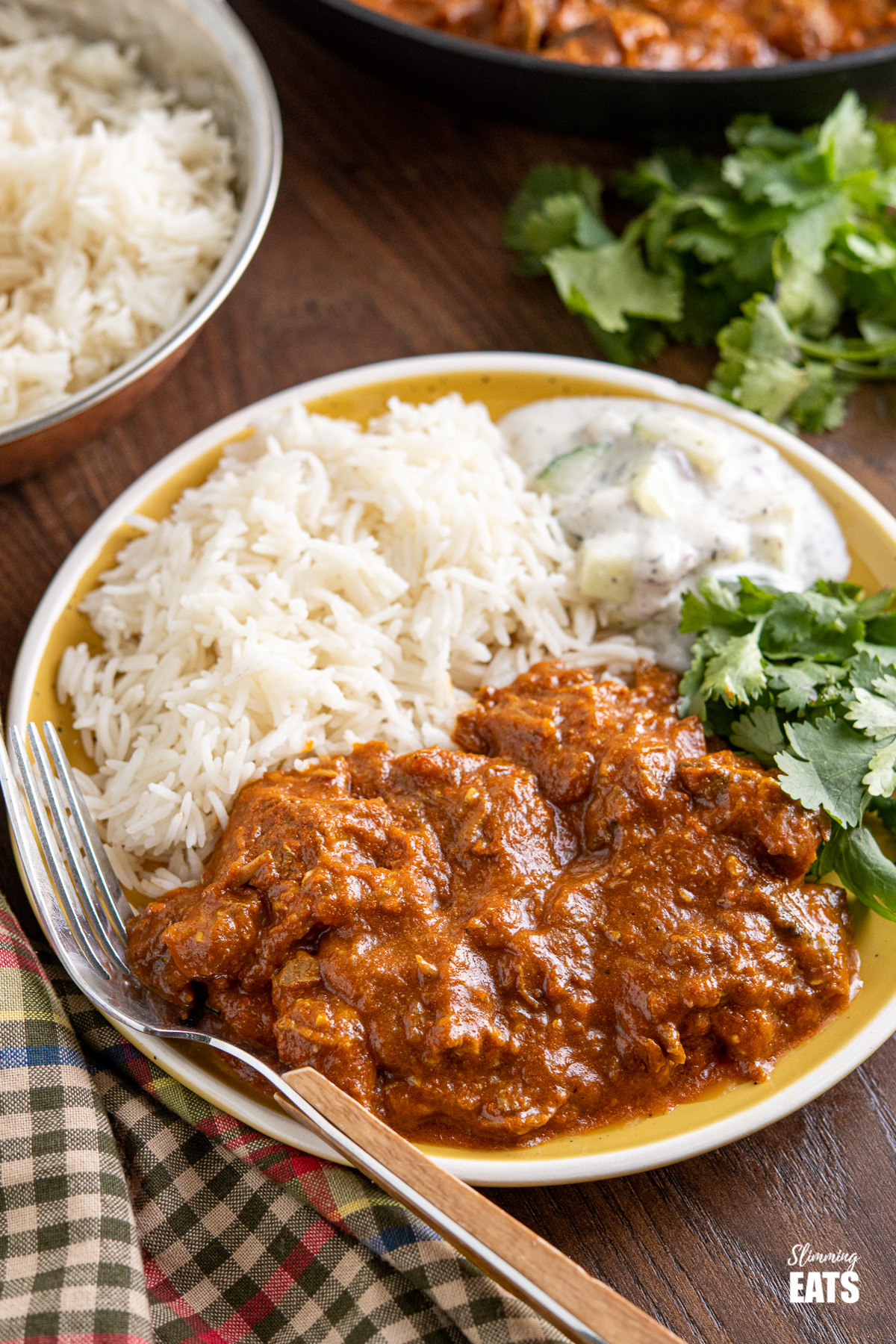 Lamb Rogan Josh on yellow plate with rice and raita and cilantro, wooden handle fork place on the plate