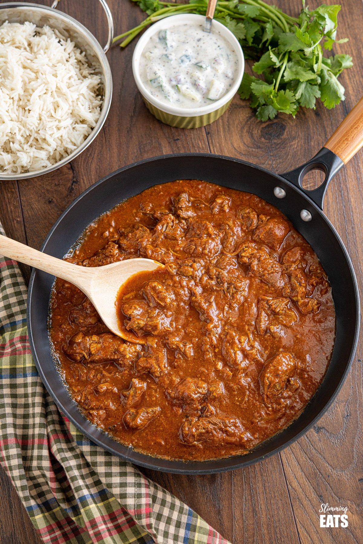 lamb rogan josh in black frying pan with wooden handle, rice, raita and cilantro in background