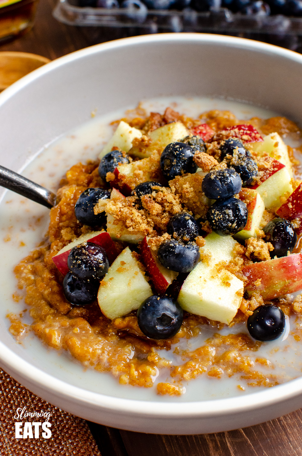 pumpkin oatmeal in grey bowl topped with blueberries, apple and crumbled biscuit