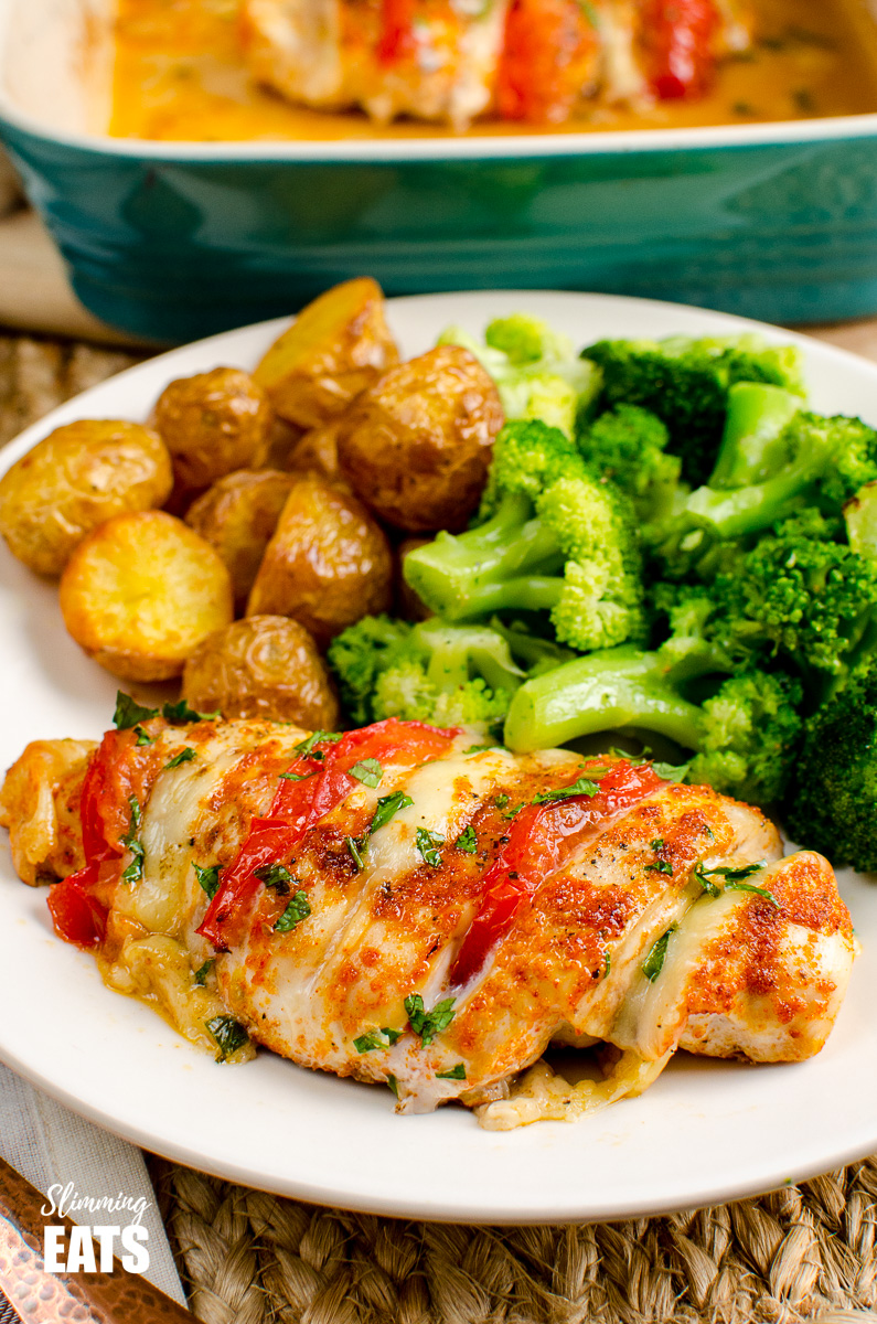 tomato and mozzarella hasselback chicken on white plate with golden potatoes and broccoli
