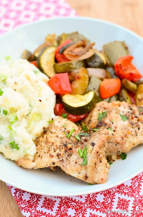 black pepper chicken on white plate with roasted vegetables