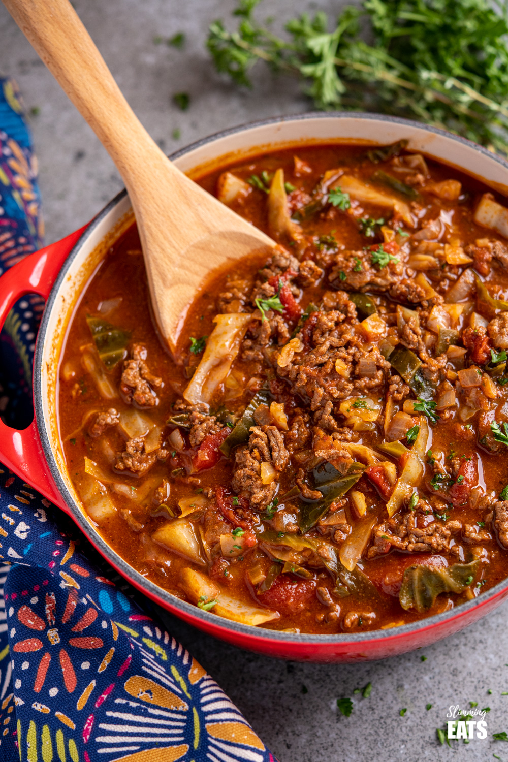close up of Beef and Cabbage Soup in cerise le creuset casserole pan with wooden spoon