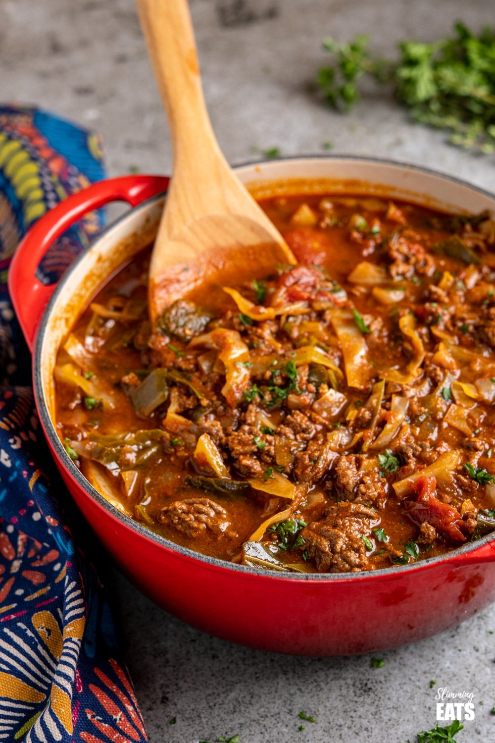 Beef and Cabbage Soup in cerise le creuset casserole pan with wooden spoon