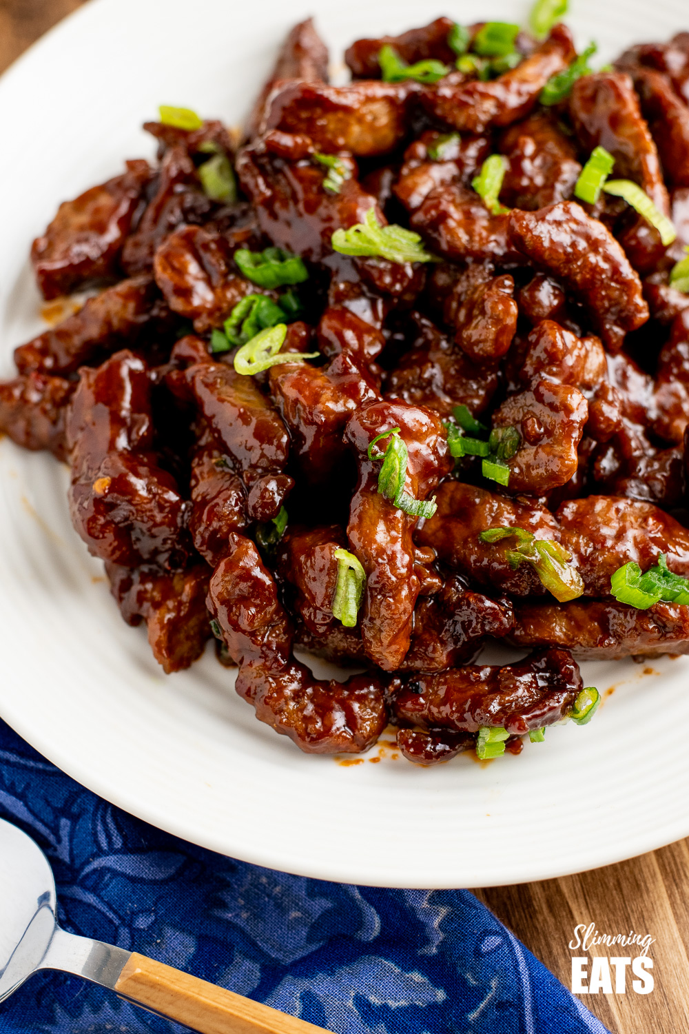 close up of sweet chilli beef on white plate
