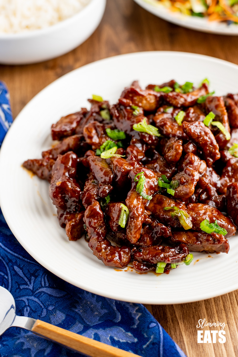 sweet chilli beef on white plate with rice and veg in background