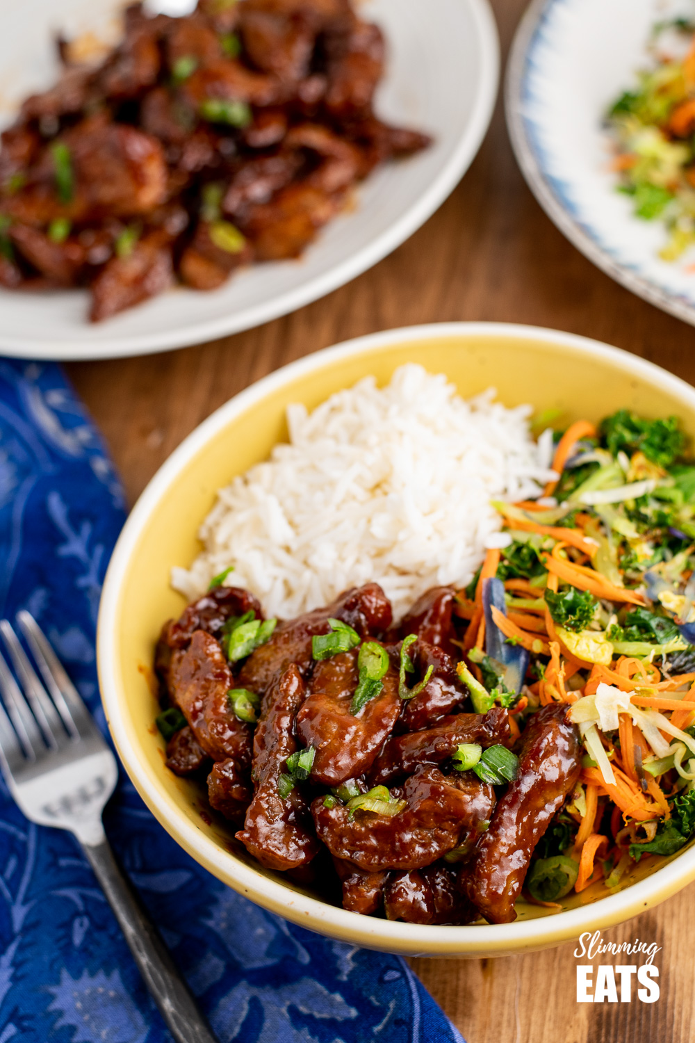 sweet chilli beef in yellow bowl with vegetables and rice.