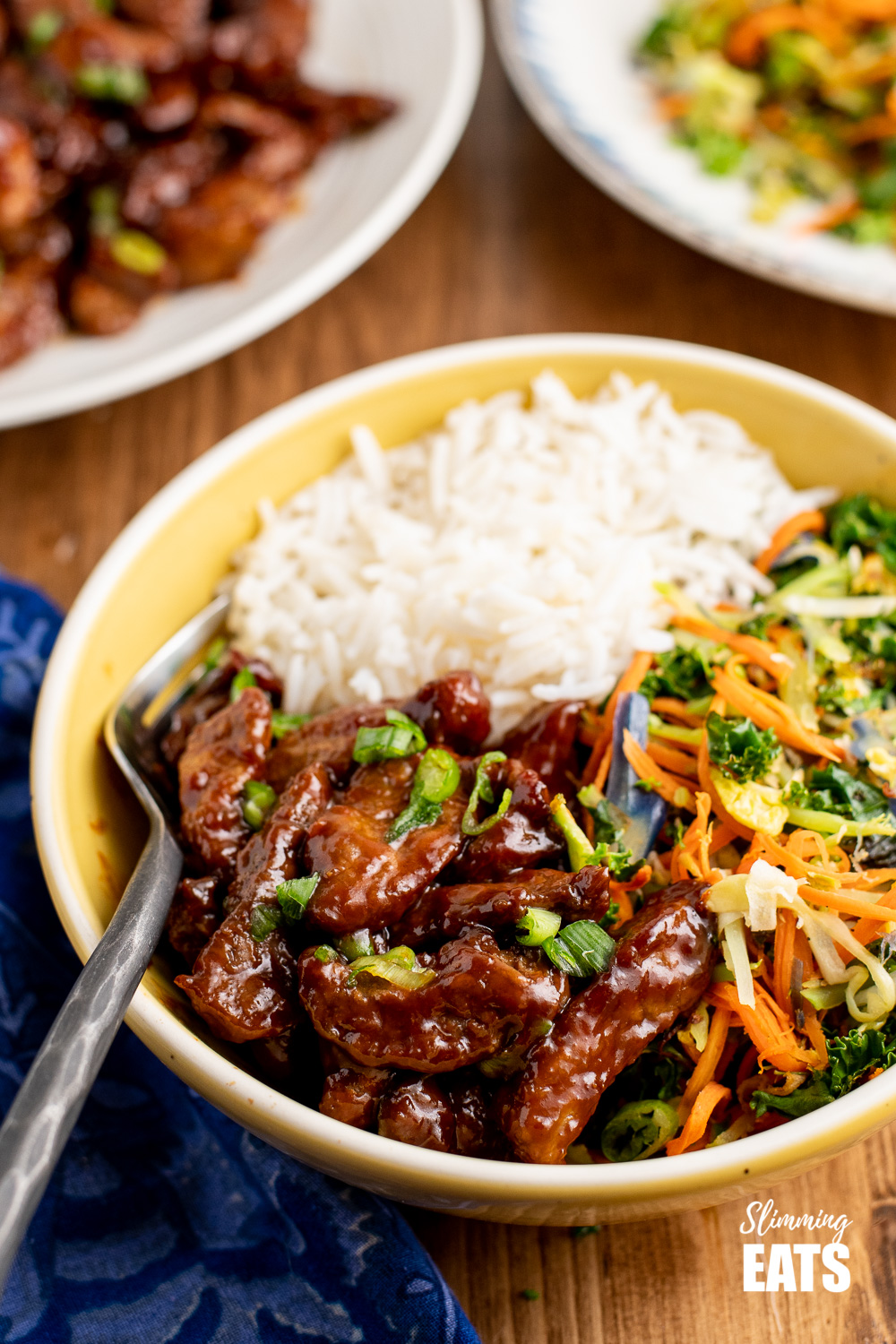 close up of sweet chilli beef in yellow bowl with rice and vegetables