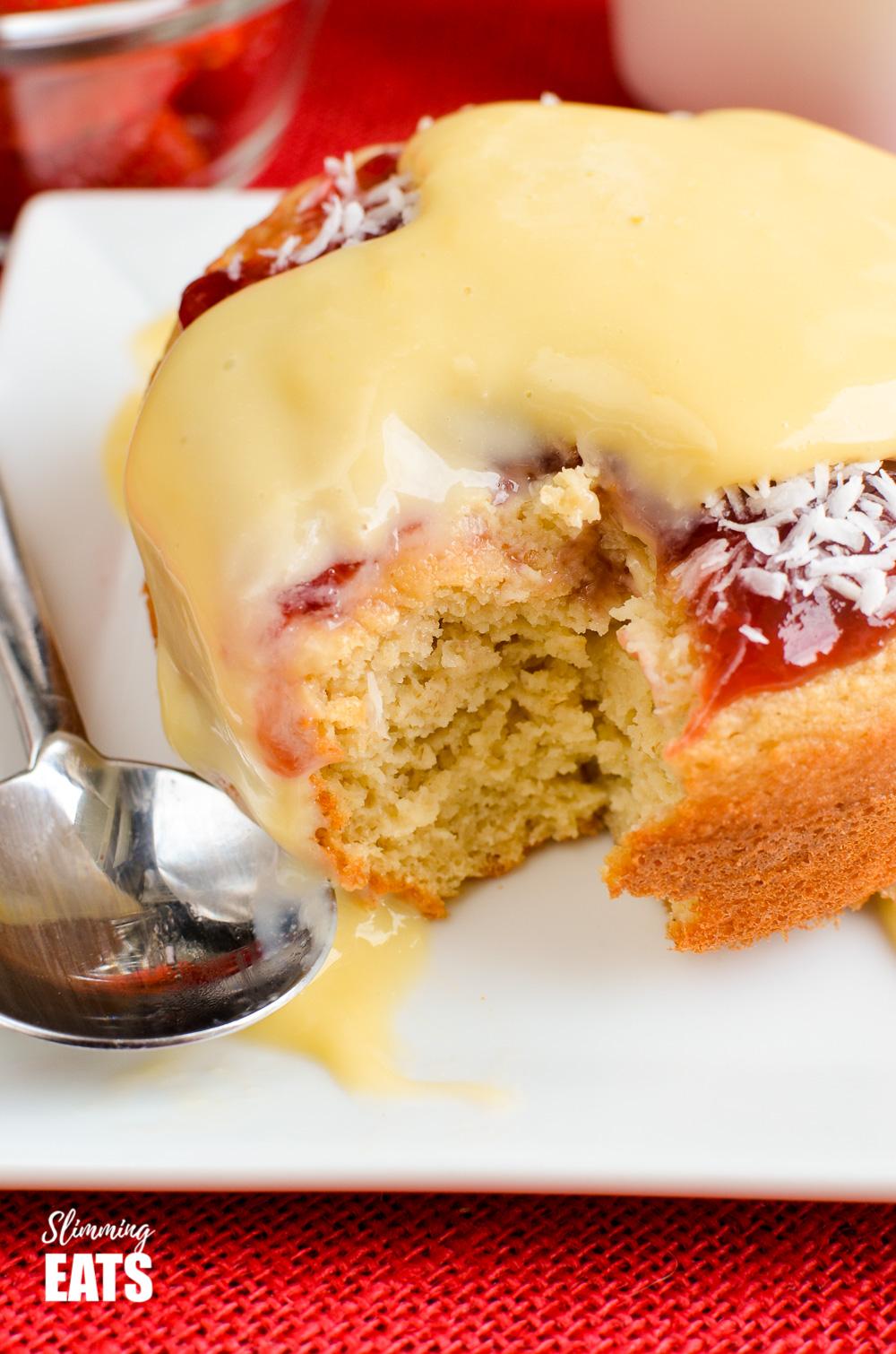 part eaten jam and coconut sponge cake on white plate
