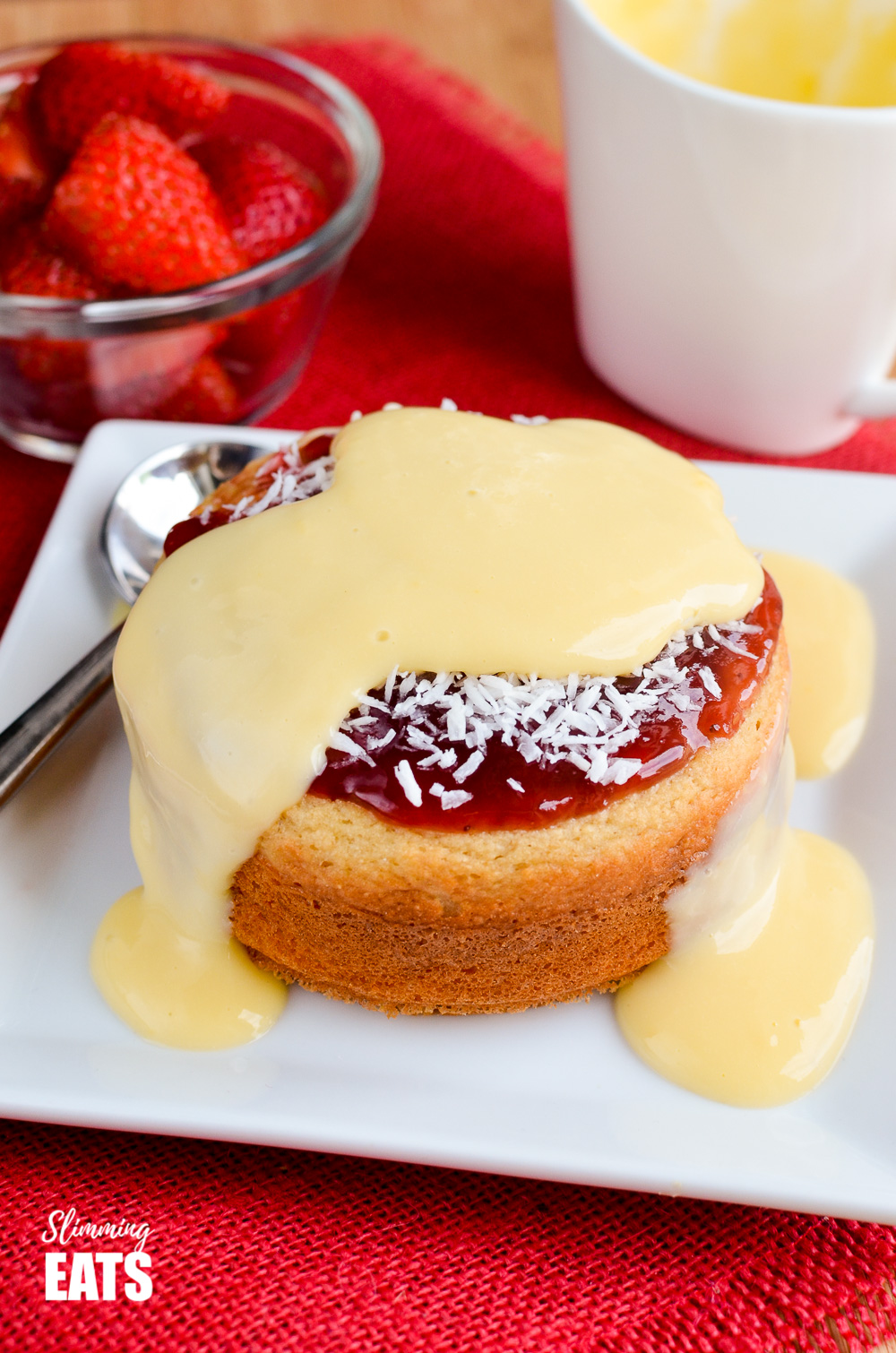 custard over jam and coconut sponge cake on white plate