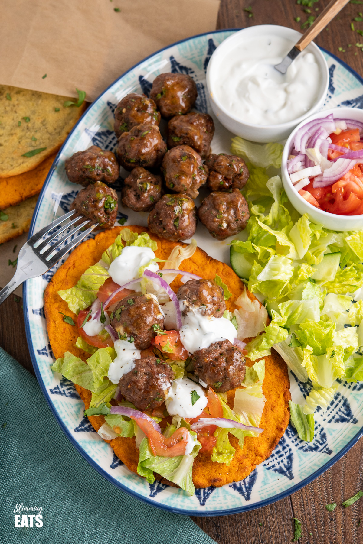 lamb kofta with sweet potato flatbread on oval patterned plate with salad and tzatziki