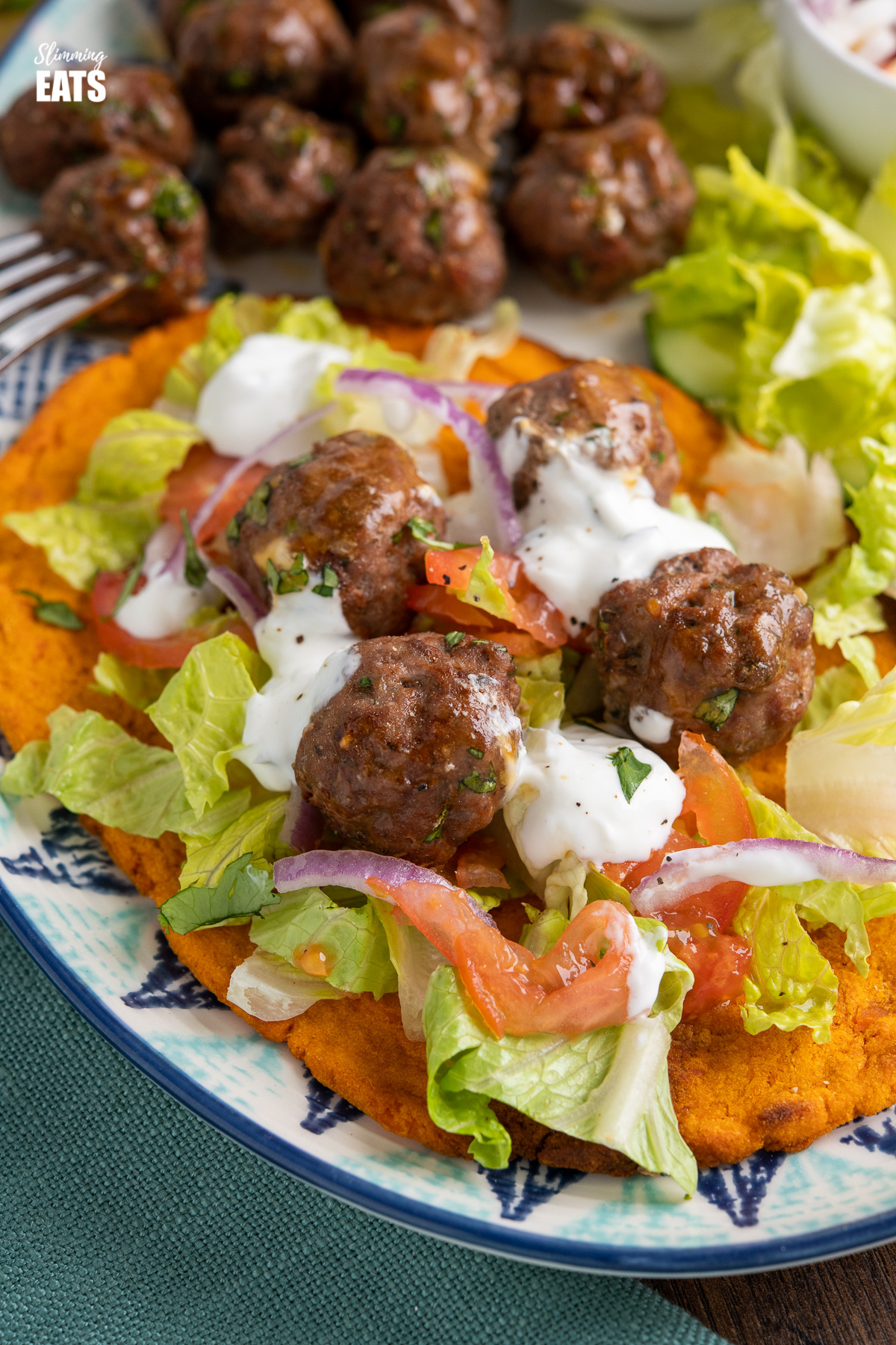 close up of lamb kofta drizzled with tzatziki on sweet potato flatbread with salad