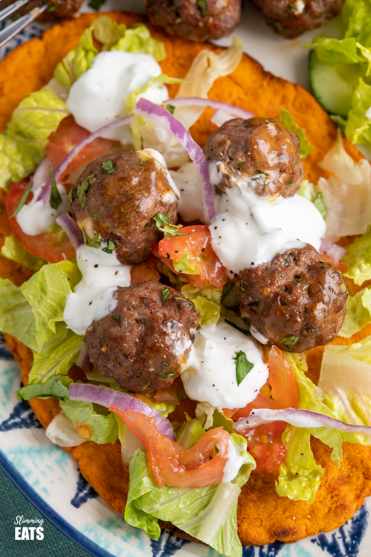 close up of lamb kofta meatballs drizzled with tzatziki