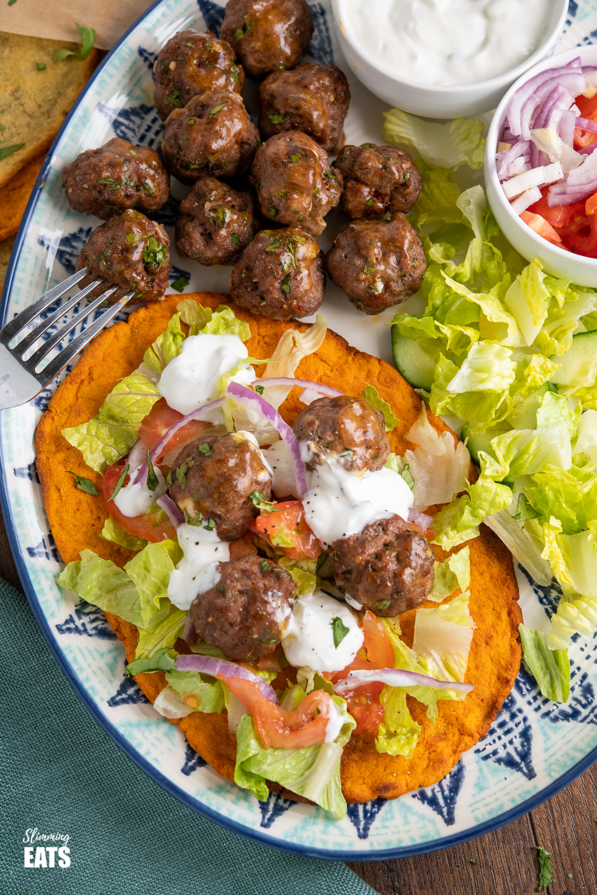 lamb kofta drizzled with tzatziki over salad on sweet potato flatbread