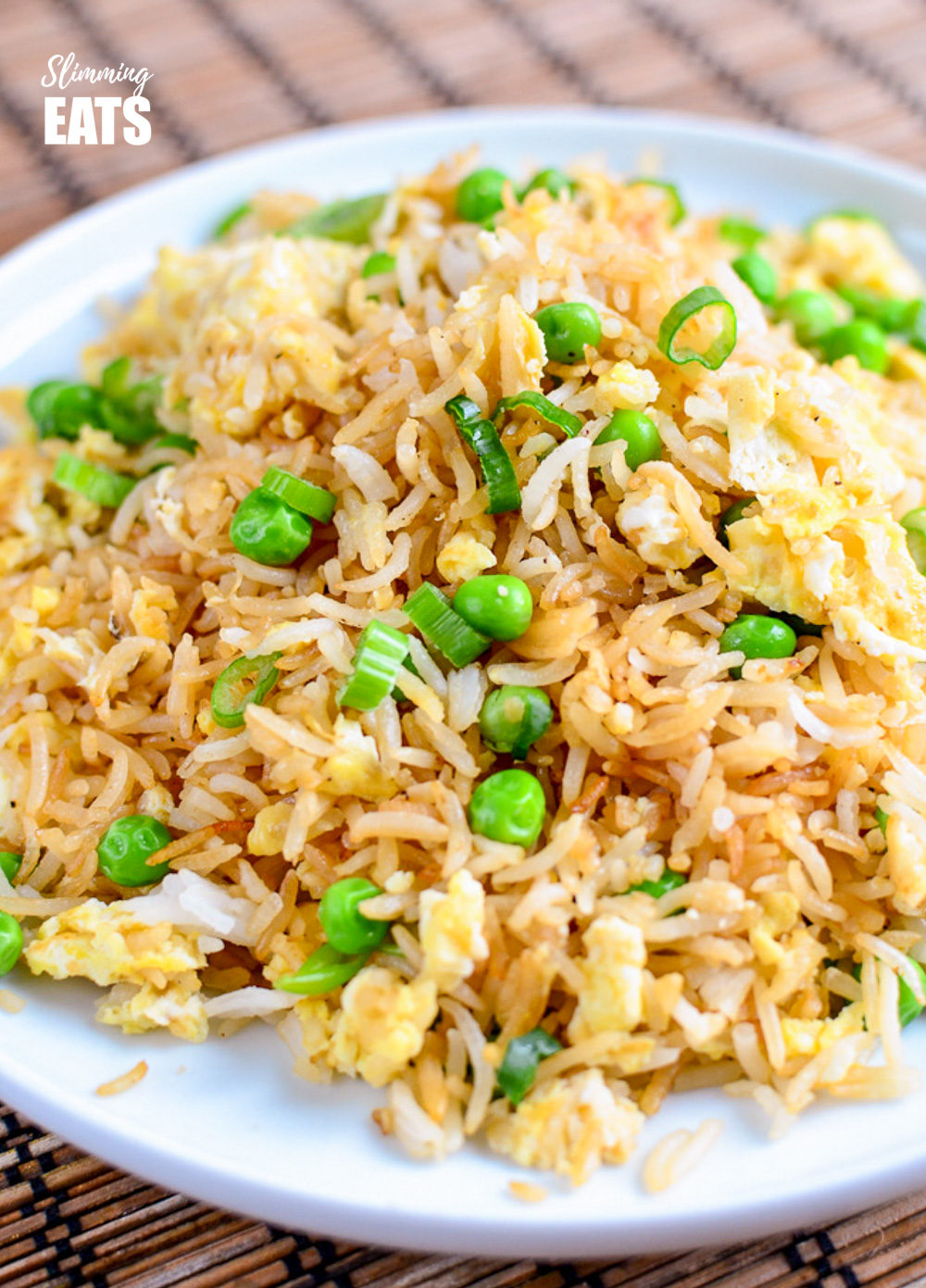 egg fried rice on a white plate on a bamboo mat