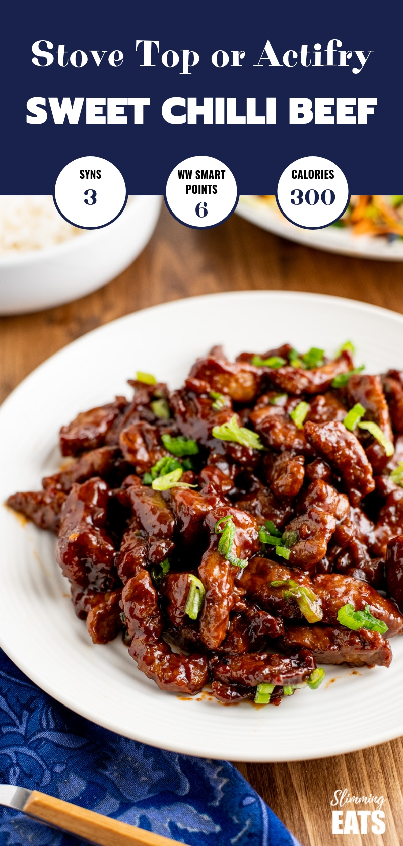 sweet chilli beef on a white plate with chopped spring onions, rice and veg in background pin