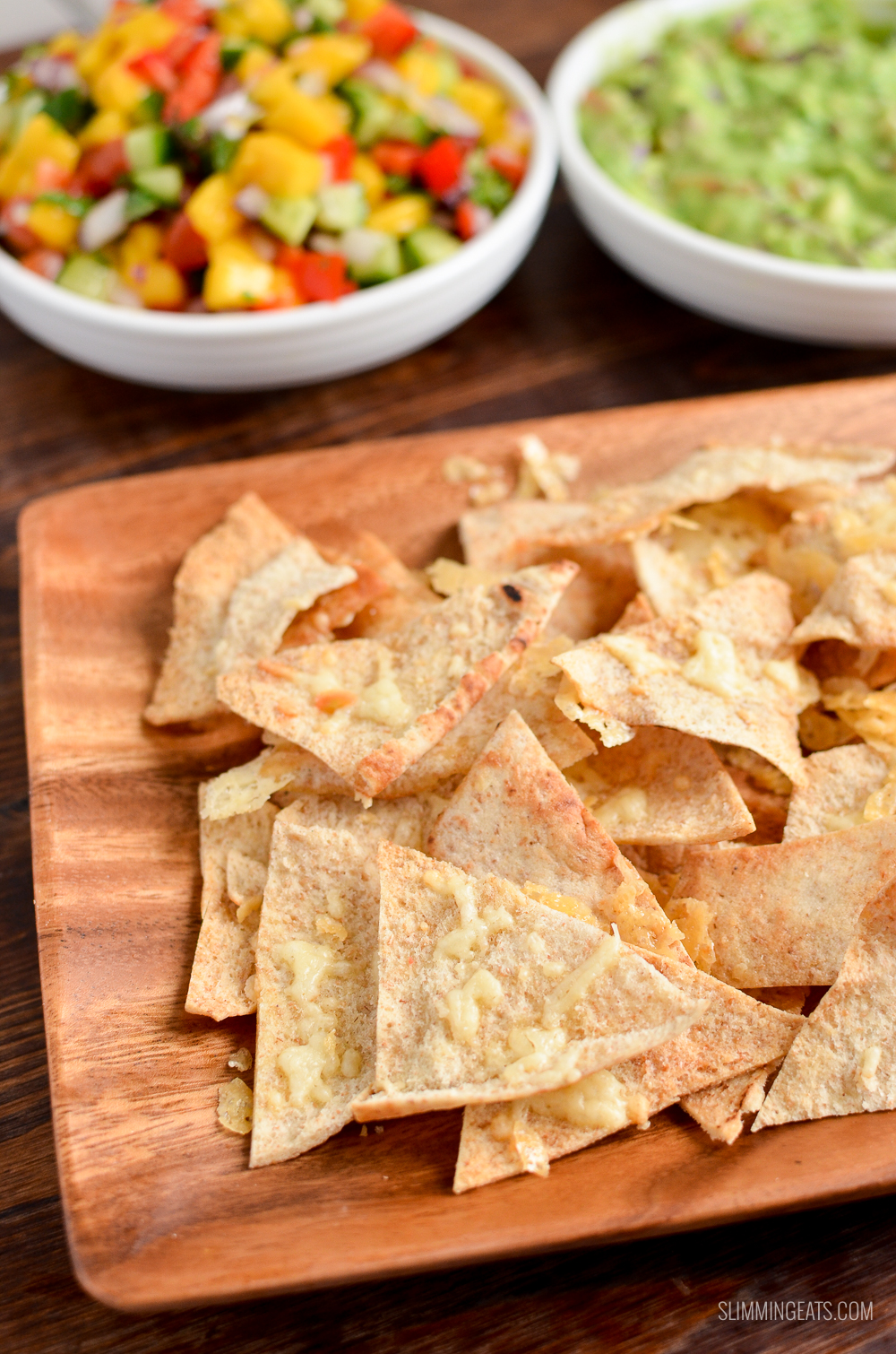 cheddar pita chips on a wooden plate with mango Salsa and guacamole